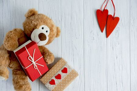 Greeting card for birthday, mothers day, Valentines day. Toy bear with hearts, gift boxes on a light wooden background.