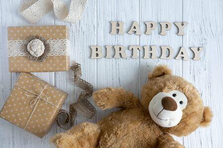 Inscription Happy Birthday. Toy bear, boxes with gifts and a congratulatory inscription happy birthday. Фото со стока