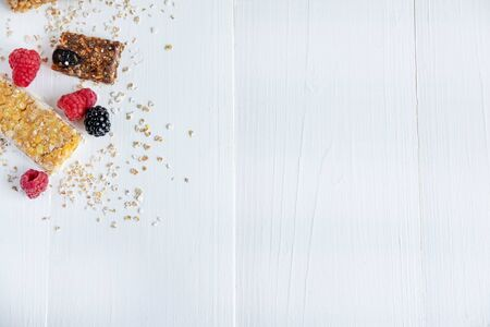 Granola for weight loss with raspberry berries. Background for text with fitness bars and raspberries jagolis on a white wooden background