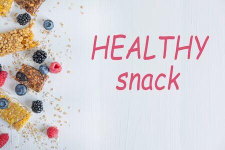 Healthy snacks. Photo of energy cereal bars with fresh raspberries, blueberries, blackberries.