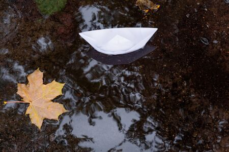 A puddle with autumn yellow leaves and a paper ship. Autumn rains and fall foliage