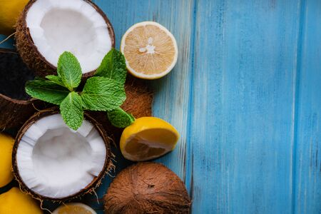 Chopped coconut halves with lemon and mint leaves on a blue wooden background. Tropical exotic background with coconut citruses and place for copy space.