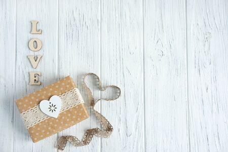 Inschrift Liebe aus Holzbuchstaben. Hölzerner heller Hintergrund mit Geschenkbox und Spitze. Rahmen für Grußkarten Standard-Bild
