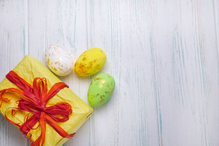 Easter background. Easter multi-colored eggs, gift box on a light wooden background with a place for copy space.