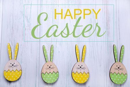 Happy easter. The inscription on the greeting Easter card with eggs, hares on a light wooden background