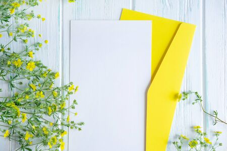 Mock up template with yellow wildflowers on a wooden background. Frame for an inscription, text with flowers.