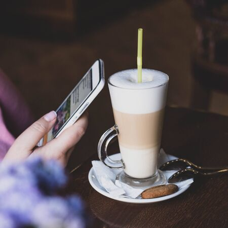 Internet surfing. A girl in a cafe over a cup of coffee reads news on social networks. G