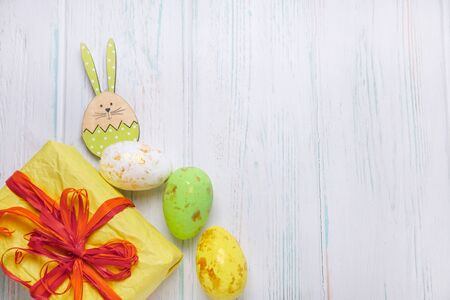 Easter backgrounds for greeting lettering, promotions. Gift box and easter eggs on a light wooden background with figures of wooden rabbits. 版權商用圖片