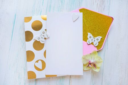 Template for an inscription with a letter envelope, notepad. White rustic background with a pink envelope and gold. Stockfoto