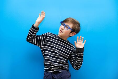 The boy with glasses is surprised at the event on a uniform blue background. Discounts and sale in the store. Emotions of surprise and joy