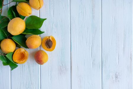 Ripe apricot fruits on a light wooden background with place for text.