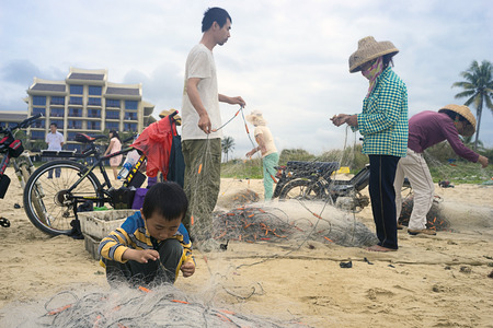 untangle: Chinese boy helps parents to untangle a fishing net