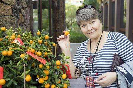 Russian tourist near Christmas tangerine tree Mandarin duck in his hand photo