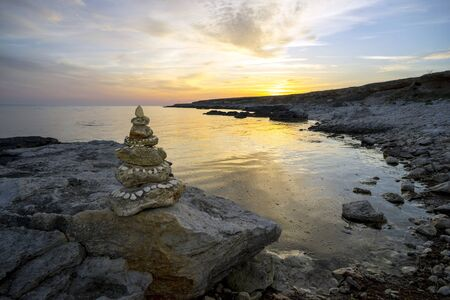 omens: Sea landscape with a pyramid of stones on the shore.