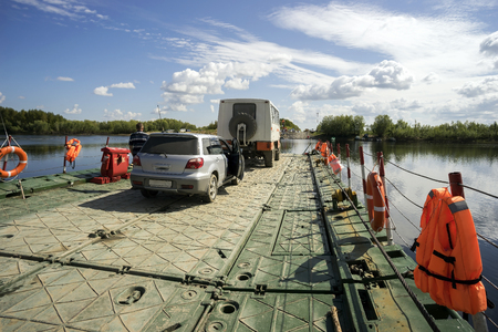 pontoon: Pontoon ferry with people and cars floating in the river . Stock Photo