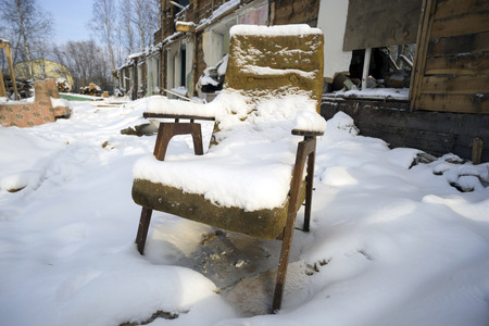 unnecessary: Old chair covered with snow in a ruined house .