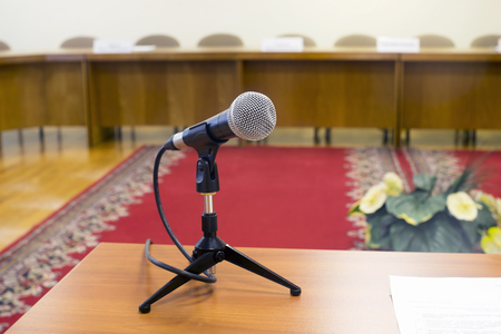 Microphone in an empty auditorium on background  red carpet.