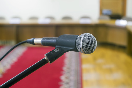 red carpet background: Microphone in  empty auditorium on background a red carpet. Stock Photo
