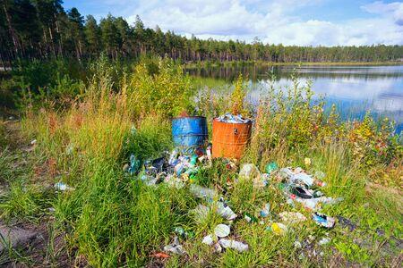 environmental sanitation: The garbage dump on  shores of clear lake . Stock Photo