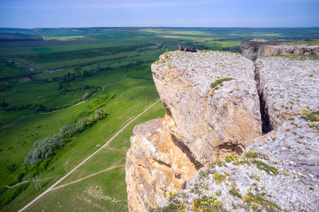 crack climbing: woman lies on the edge of a cliff in Crimea.