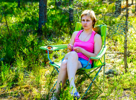 Young pensive woman sitting in a chair in the woods.