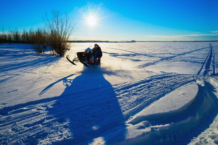 ray trace: Snowmobile flies through a snowy field on a Sunny day .