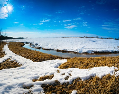 thawed: Spring landscape with a brook behind a snow mound . Siberia, Yugra.