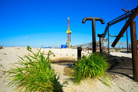 'rig out': Drilling rig with pipes sticking out and green grass. Siberia. Stock Photo