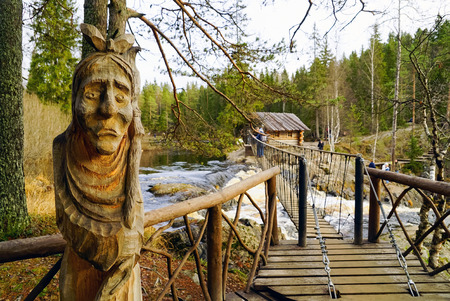 Carved wooden sculpture of an old woman near the pedestrian suspension bridge over a waterfall on the river tokhmayoki.