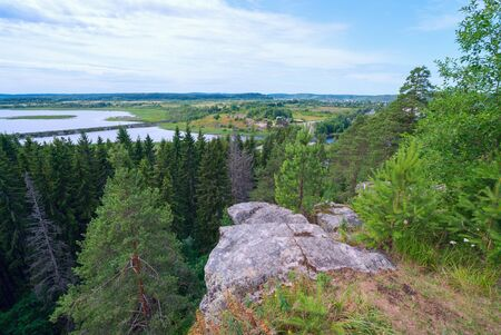 The stone cliff over the forest and river Hellenici , Karelia