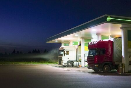 Trucks refuel at the gas station at night.