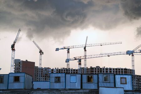 Dark clouds over the construction site and construction cranes.