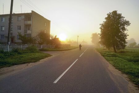 Morning fog with the rising sun on the street in the village .