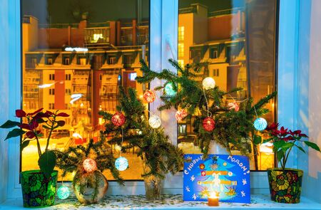 Christmas composition with fir branches lanterns and childrens drawing on the windowsill Stock fotó
