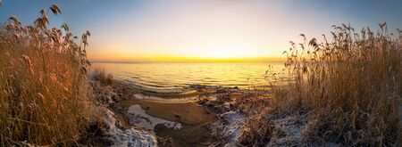 The first rays of the sun over lake Ladoga in the morning in winter. Leningrad region .Panorama.