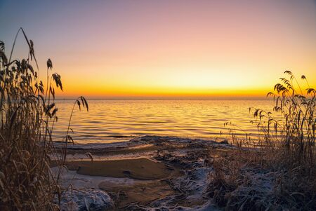 The first rays of the sun over lake Ladoga in the morning in winter. Leningrad region . Stock fotó