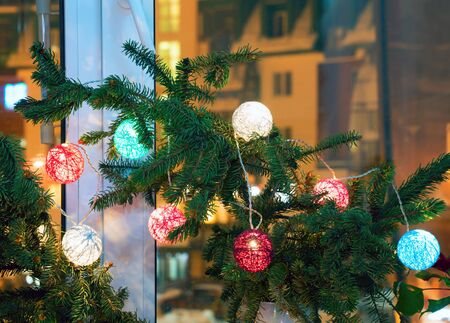 Christmas composition with fir branches and lanterns on the windowsill