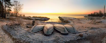 The first rays of the sun over lake Ladoga in the morning in winter. Overturned boats on a snowy beach. Leningrad region .