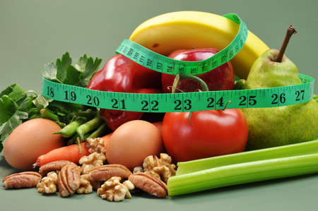 weight loss plan: Group of wholesome, organic food, including pear, apple, tomato, eggs, nuts, pecans, walnuts, carrot, banana, and apple, for a healthy diet or slimming New Year resolution  Stock Photo