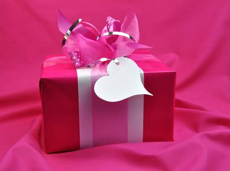 Hot candy pink gift wrapped Valentine, Christmas or birthday present with ribbons and white gift tag, against folds of pink fabric background  photo