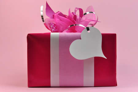 A pretty pink present gift wrapped with lots of pink bows with a white heart shape gift tag isolated against a pale pink background  photo
