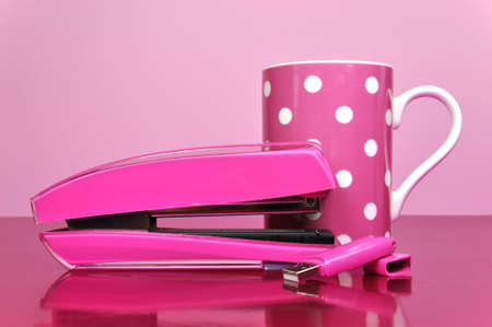 Pretty in Pink office accessories, stapler, pen drive, and polka dot mug, on a pink desk against a pale pink background. photo