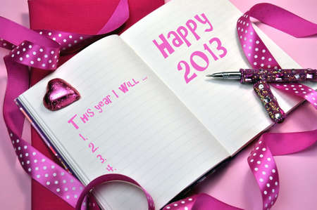 2013 Happy New Year message in pink diary with New Year Resolutions list on pink background with pink heart chocolate, polka dot ribbon and pink bling writing pen. Stock Photo - 16679329