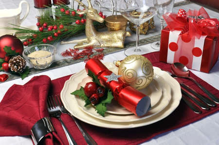 Modern and stylish Christmas dinner table setting including plates, glasses and placemats, bon bons and Christmas decorations Landscape  horizontal  orientation  photo