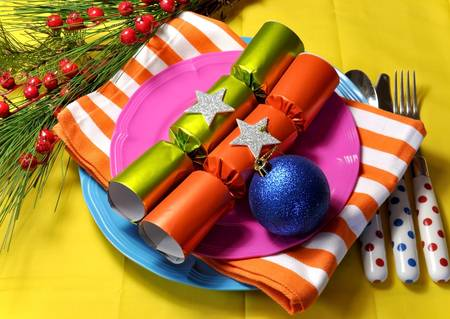 bon: Bright and colorful Christmas table setting with plates, forks and knives, Christmas Bon Bons Crackers with decorations for a lively, stylish and fun holiday party atmosphere