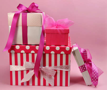 Stack of pretty feminine pink presents and gifts with ribbons and bows, stripes and polka dot, for Valentine, Christmas, holiday giving, birthday, or special occasion for a special lady  Stock Photo