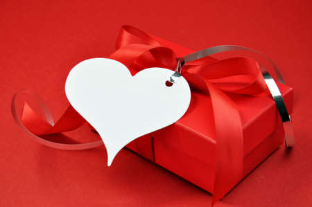 Red Valentine or Christmas present gift box with white heart gift tag on red texture background. photo