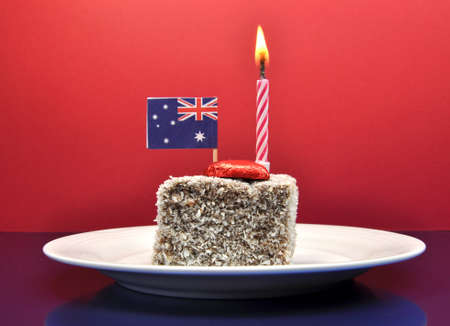 lamington: Australia Day January 26, celebrate with tradional Aussie tucker food, lamington cake with candle and an Australian flag