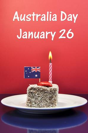 lamington: Australia Day January 26, celebrate with tradional Aussie tucker food, lamington cake with candle and an Australian flag, with text