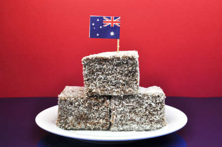 downunder: Australia Day January 26, celebrate with tradional Aussie tucker food such as lamingtons, with an Australian flag  Stock Photo